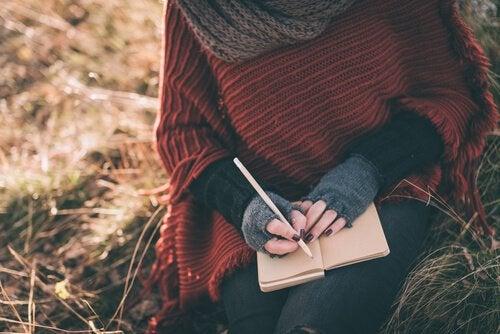 Person skriver ting ned i bog