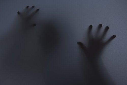 Skygge af person med hænder på vindue er plaget af epidemi af angst