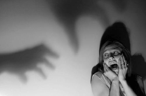 Angst kvinde ser skygger på væg