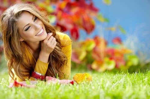 Kvinde på græs smiler og er glad på grund af mindfulness