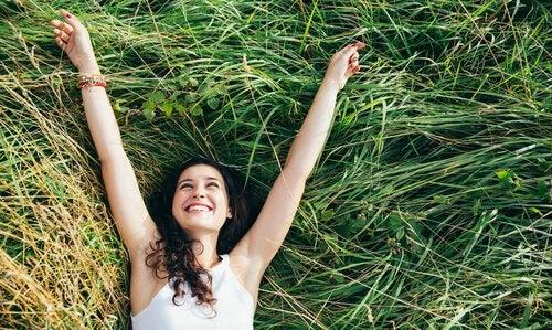Smilende kvinde i græs lever et simpelt liv
