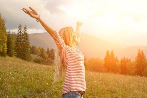 Kvinde med hænderne over hovedet er glad på grund af psykologisk velvære