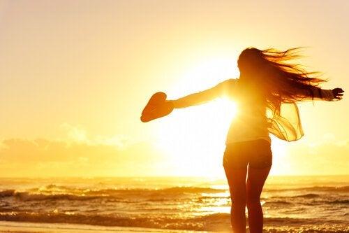 Fri kvinde på strand for solnedgang