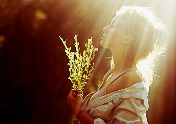 Kvinde i sollys med blomster