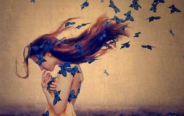 Nøgen kvinde dækket af sommerfugle viser sin følsomhed