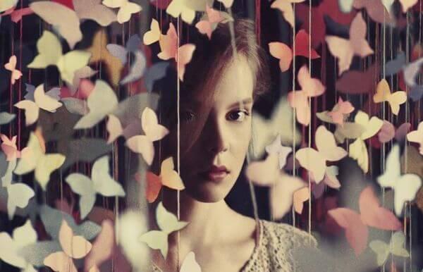 Kvinde bag gardin af sommerfugle