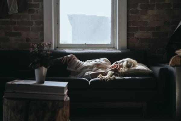 Kvinde sover på sofa og viser, hvordan følelser påvirker vores krop gennem psykosomatiske lidelser