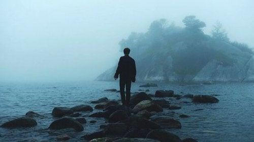Mand går alene på store sten i vandkant