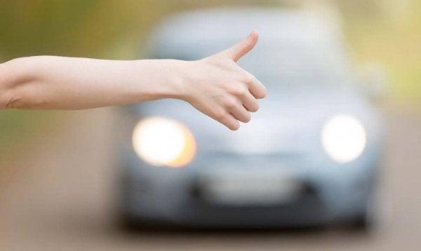 Tommelfinger i vejret foran bil viser, at man kan bede om ting med håndtegn