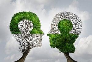To træer formet som hoveder og puslespil viser, hvordan man kan fuldende hinanden ved at sætte sig selv i andres sted