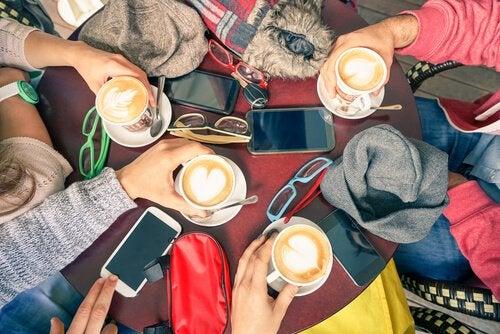 Venner drikker kaffe med mobilet liggende på bordet