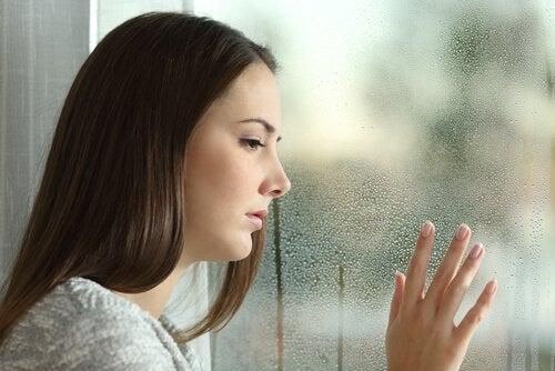 Trist kvinde ved vindue efter ødelagt forhold