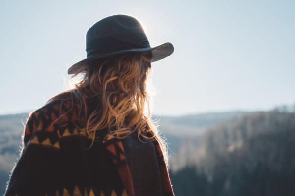 Kvinde med hat foran landskab
