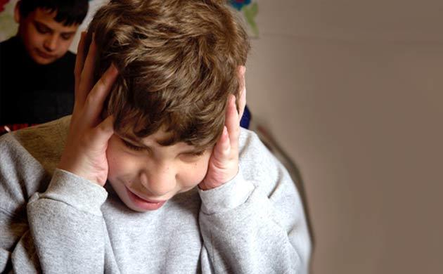 Dreng med autisme tager sig til hovedet