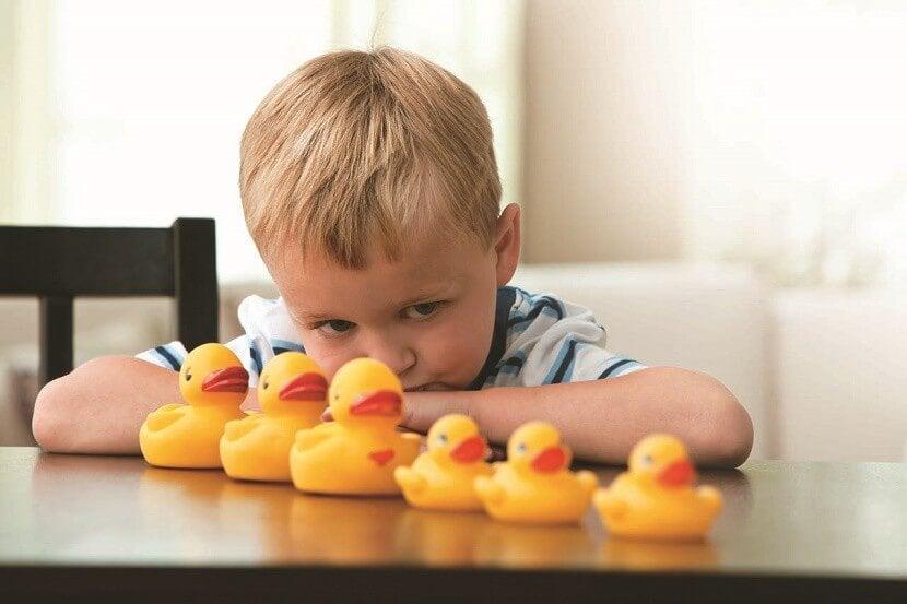 Dreng med autisme arrangerer legetøj