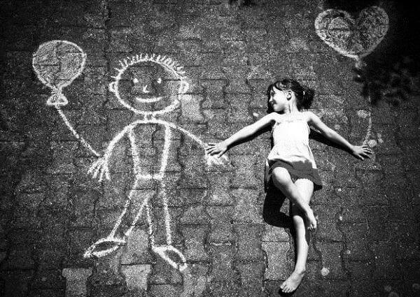 Pige ligger på jord med menneske af kridt
