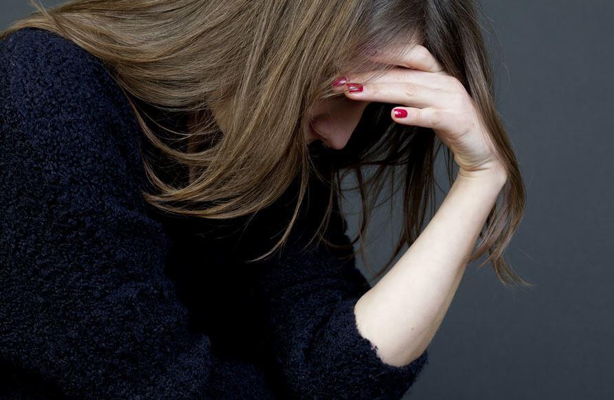 Bekymret kvinde tager sig til hovedet, træt af problemløsning