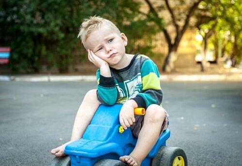 Trist dreng på legetøjsbil oplever rigt barn syndrom