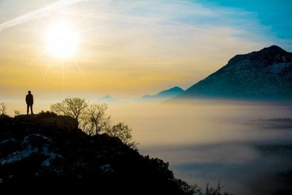 Mand på toppen af bjerg er igang med mindfulness