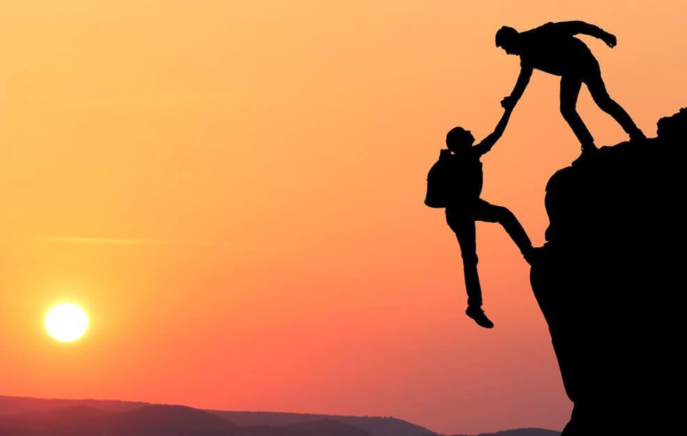 Venner hjælper hinanden op på bjerg, da tillid gør man sig fortjent til
