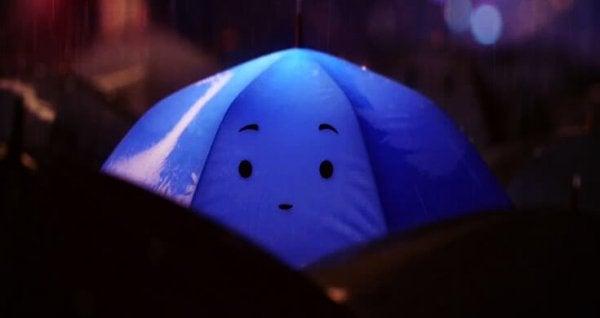 Blå paraply med ansigt symboliserer person med autisme