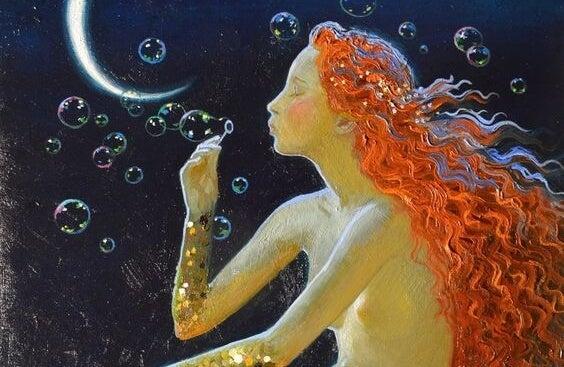 Kvinde med langt hår blæser sæbebobler