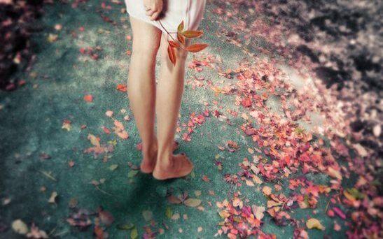 Barfodet kvinde på jord med blade