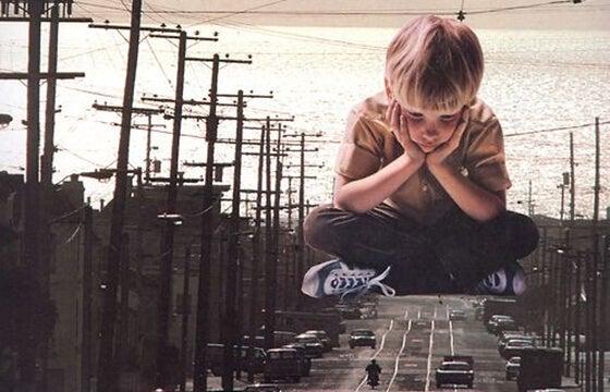 Dreng sidder og venter i miniatureby