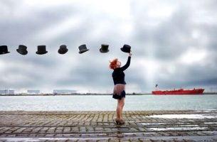 Person rækker ud efter flyvende hatte
