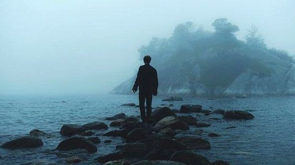 Mand går på sten ved hav