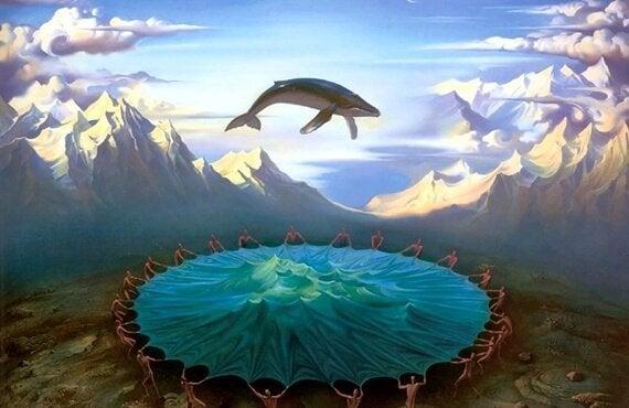 Hval hopper over sø foran bjerge