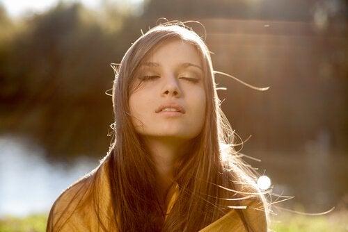 Kvinde med lukkede øjne er ved at udøve mindfulness
