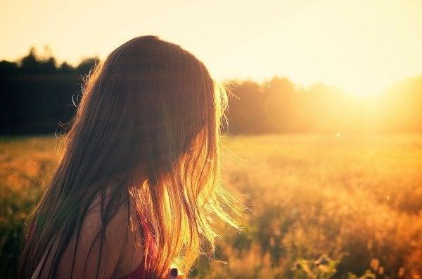 Kvinde på mark i sollys nyder lykke