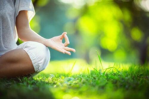 Kvinde mediterer i natur for at skabe en kilde til positive følelser