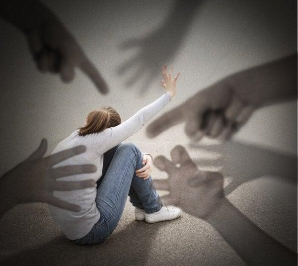 Hænder peget på kvinde som symbol på misundelse