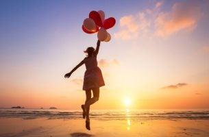 Pige med balloner på strand hopper op i luften for at finde motivationen
