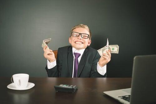 Dreng ved skrivebord med penge lider under rigt barn syndrom