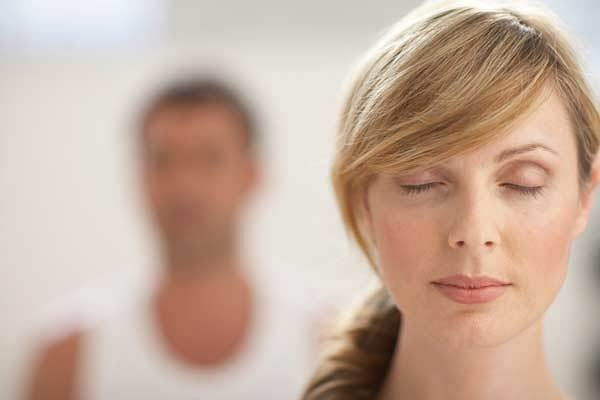 Rolig kvinde med lukkede øjne udøver mental kontrol