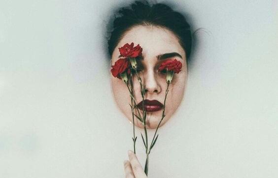 Kvinde med roser foran øjne som symbol for følelsesmæssige tømmermænd