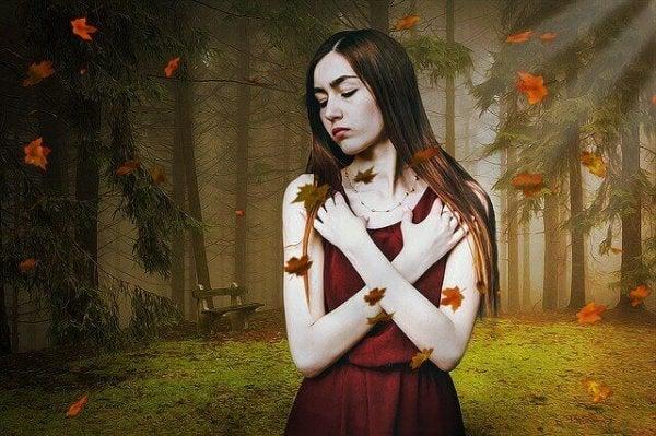 Kvinde holder om sig selv i skov