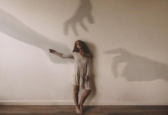 Kvinde på væg med hænders skygger
