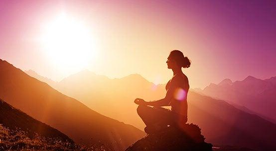 Person på bjerg ved solopgang anvender mantraer til meditation