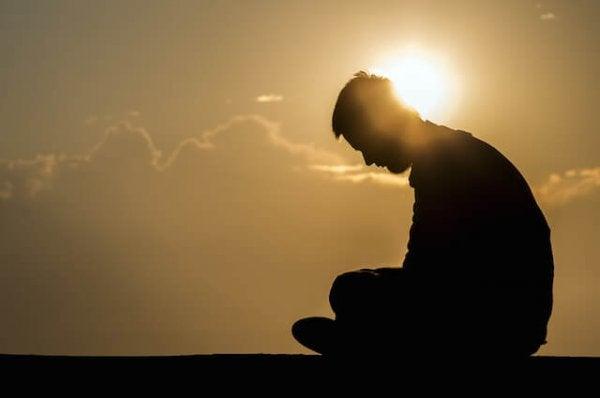Person sidder med bøjet hoved foran sol, trist over passiv vold