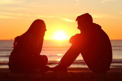 Par sidder og snakker foran solopgang