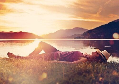 Kvinde sover foran sø og bjerge