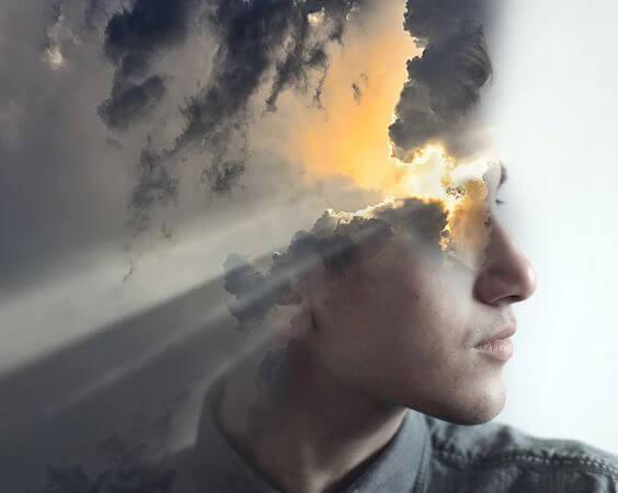 Mands ansigt, hvor solen bryder igennem skyer, ønsker at sabotere sig selv