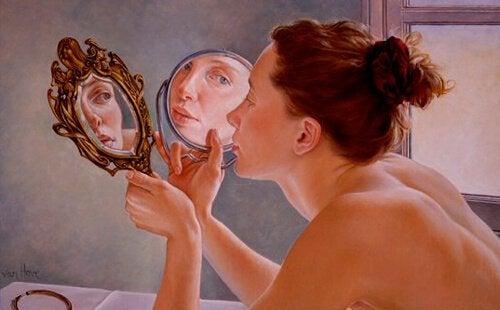 Nøgen kvinde ser sig selv i spejl