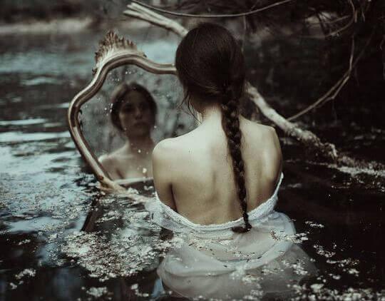 Kvinde i flod med stort spejl