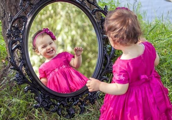 Pige med selvsikkerhed smiler til sig selv i spejl
