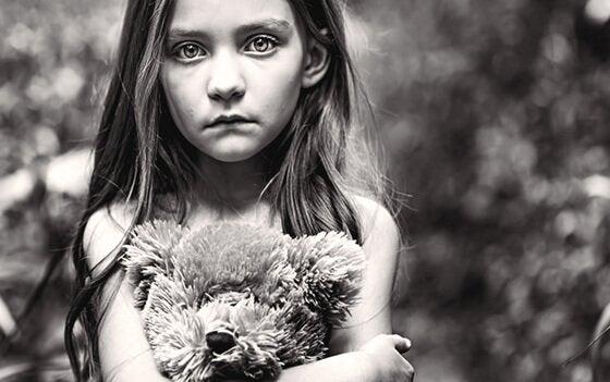 Trist pige krammer bamse som eksempel på de glemte børn